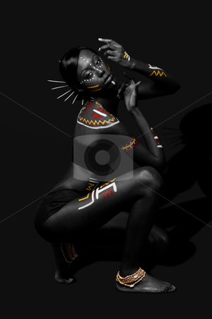 Tribal beauty woman with makeup stock photo, Beautiful exotic African female fashion with tribal yellow red and white makeup cosmetics and sticks in hair, in cultural dance position. by Paul Hakimata