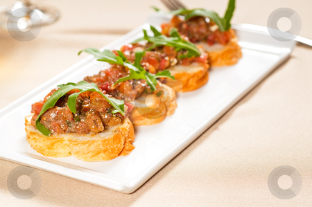 Italian bruschetta stock photo, fresh tipycal italian bruschetta with tomato and arugula on top by Francesco Perre