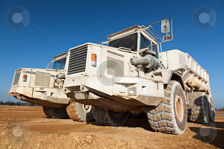 Dump Trucks stock photo, A couple of dump truck on dirt against a deep blue sky by Fred DE BAILLIENCOURT