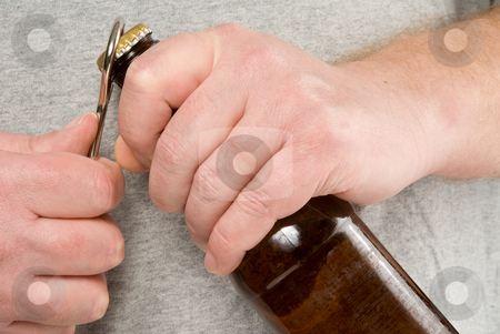 Opening a Beer stock photo, A person using a bottle opener to open a beer. by Robert Byron