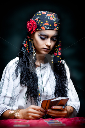 A portrait of a gypsy fortune teller. stock photo, a portrait of a gypsy fortune teller, sitting at a table and looking at the tarot cards that she holds in her hands. by dan comaniciu