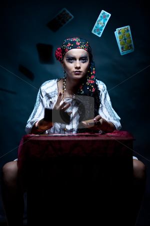 A portrait of a gypsy fortune teller throwing the tarot cards. stock photo, a portrait of a gypsy fortune teller, sitting at a table and hrowing the tarot cards that she holds in her hands towards the camera. by dan comaniciu
