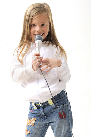 Blond girl singing using a microphone stock photo, young pretty blond girl singing using a microphone in studio by Ansunette