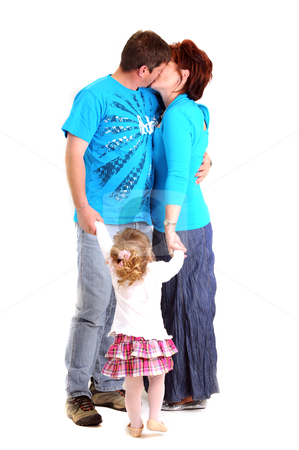Young couple kissing and holding hands with their daughter while she is watching stock photo, young couple kissing and holding hands with their daughter while she is watching by Ansunette