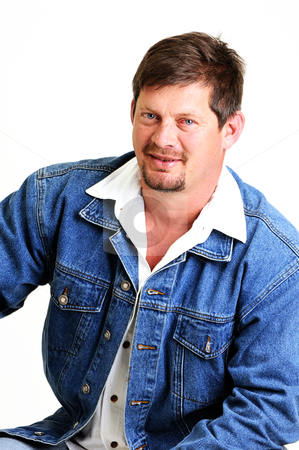 Portrait of handsome male model with beard stock photo, portrait of handsome male model with beard and smiling wearing a jeans jacket by Ansunette