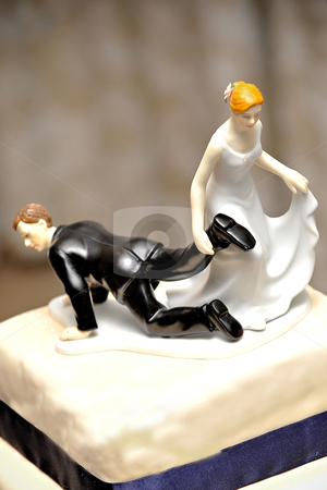 Wedding figurine on cake with bride dragging the groom doll by the feet stock photo, wedding figurine on cake with bride dragging the groom doll by the feet to the church symbolically by Ansunette