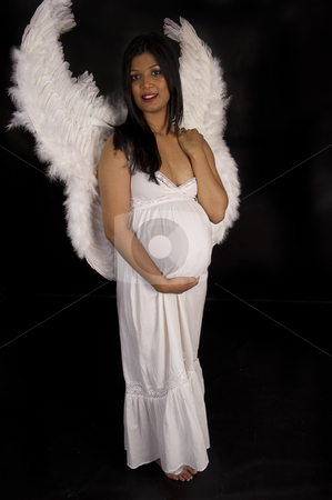 A beautiful pregnant Indian woman in white dress and angel wings smiling on black backdrop stock photo, A beautiful pregnant Indian woman in white dress and angel wings smiling on black backdrop by Ansunette
