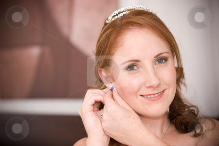 Sexy beautiful bride inserting her earrings in whilst smiling stock photo, red head sexy beautiful bride inserting her earrings in whilst smiling by Ansunette