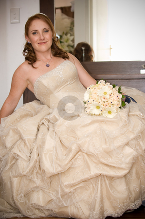 Bride sitting leaning on arm smiling and holding white bouquet stock photo, red head sexy beautiful bride sitting with cleavage visible and leaning on her arm while smiling and holding her white flower bouquet by Ansunette