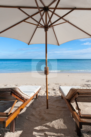Deckchairs on the beach stock photo, Deckchairs and parasol on the white sand beach facing the lagoon by Pierre-Yves Babelon