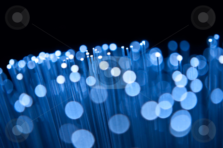 Optical abstract stock photo, Close up on the ends of many illuminated blue fibre optic strands with many unfocussed bokeh effects against black background. by Samantha Craddock
