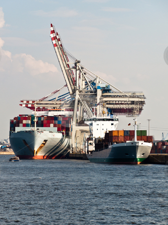 Container Ships in Hamburg Harbor, Germany stock photo, Large container ships being unloaded in Hamburg Dock, Germany. Hamburg is the second biggest container port in Europe and can serve the largest ships. by Frank G?
