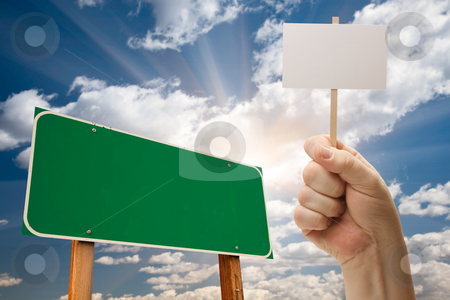 Blank Green Road Sign and Man Holding Poster on Stick  stock photo, Blank Green Road Sign and Man Holding Poster on Stick Over Blue Sky and Clouds. by Andy Dean