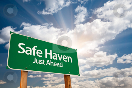 Safe Haven Green Road Sign and Clouds stock photo, Safe Haven Green Road Sign with Dramatic Clouds, Sun Rays and Sky. by Andy Dean