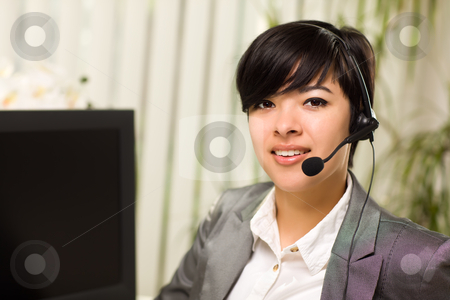 Attractive Young Woman Smiles Wearing Headset stock photo, Attractive Young Woman Smiles Wearing Headset Near Her Computer Monitor. by Andy Dean