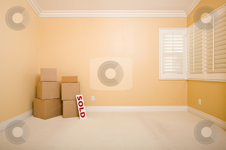 Moving Boxes and Sold Real Estate Sign on Floor stock photo, Moving Boxes and Sold Real Estate Sign on Floor in Empty Room with Copy Space on Blank Wall. by Andy Dean