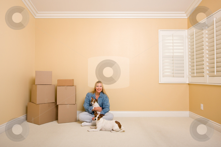 Pretty Woman and Dogs with Moving Boxes in Room on Floor stock photo, Pretty Woman and Dogs Sitting on the Floor with Moving Boxes in Empty Room by Andy Dean