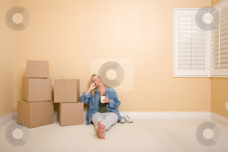 Happy Woman Relaxing Next to Boxes on Floor with Cup stock photo, Pretty Woman Sitting on Floor with Cup Next to Moving Boxes in Empty Room. by Andy Dean