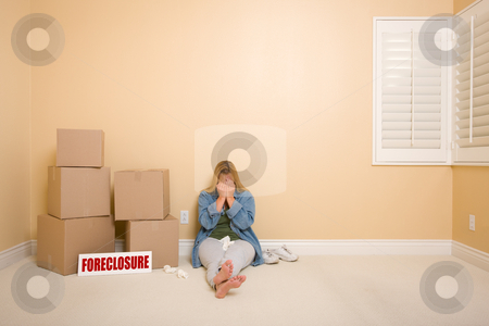 Upset Woman on Floor Next to Boxes and Foreclosure Sign stock photo, Upset Woman with Tissues on Floor Next to Boxes and Foreclosure Real Estate Sign in Empty Room. by Andy Dean