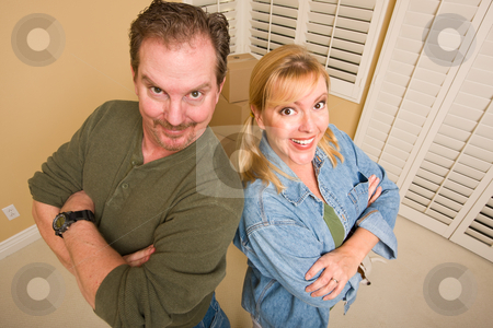 Goofy Couple and Moving Boxes in Empty Room stock photo, Smiling Goofy Couple and Moving Boxes in Empty Room. by Andy Dean