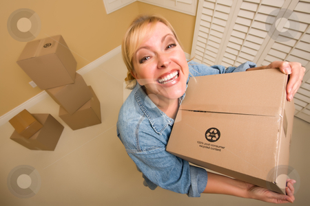 Excited Woman Holding Moving Boxes in Empty Room stock photo, Excited Woman Holding Moving Boxes in Empty Room Taken with Extreme Wide Angle Lens.  by Andy Dean