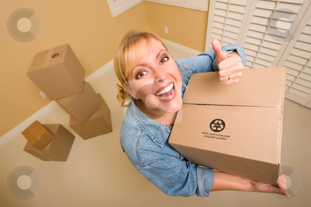 Happy Thumbs Up Woman Moving Boxes stock photo, Excited Woman with Thumbs Up and Moving Boxes in Empty Room Taken with Extreme Wide Angle Lens.  by Andy Dean