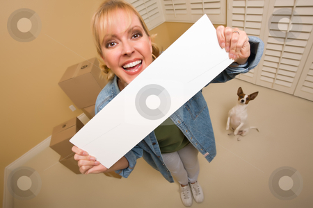 Woman and Doggy with Blank Sign Near Moving Boxes stock photo, Excited Woman and Doggy with Blank Sign Near Moving Boxes in Empty Room Taken with Extreme Wide Angle Lens.  by Andy Dean