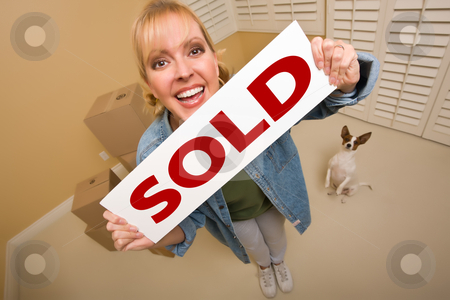 Woman and Doggy with Sold Sign Near Moving Boxes stock photo, Excited Woman and Doggy with Sold Real Estate Sign Near Moving Boxes in Empty Room Taken with Extreme Wide Angle Lens.  by Andy Dean