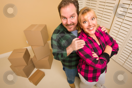 Proud Goofy Couple and Moving Boxes in Empty Room stock photo, Proud Smiling Goofy Couple and Moving Boxes in Empty Room. by Andy Dean