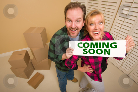 Goofy Couple Holding Coming Soon Sign in Room with Boxes stock photo, Goofy Couple Holding Coming Soon Sign in Room with Packed Cardboard Boxes. by Andy Dean