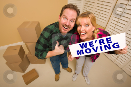 Goofy Couple Holding We're Moving Sign Surrounded by Boxes stock photo, Goofy Thumbs Up Couple Holding We're Moving Sign in Room with Packed Cardboard Boxes. by Andy Dean