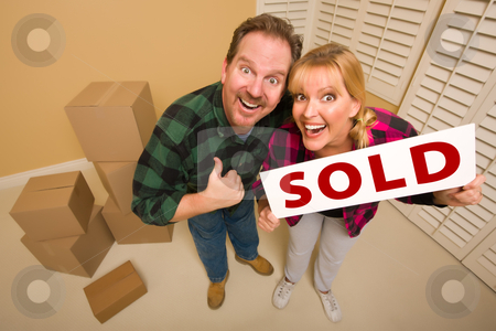 Goofy Couple Holding Sold Sign Surrounded by Boxes stock photo, Goofy Thumbs Up Couple Holding Sold Sign in Room with Packed Cardboard Boxes. by Andy Dean