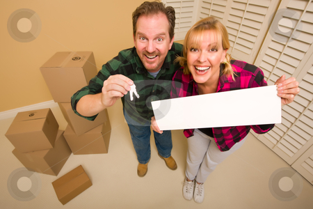 Goofy Couple Holding Keys and Blank Sign Surrounded by Boxes stock photo, Goofy Couple Holding Keys and Blank Sign in Room with Packed Cardboard Boxes. by Andy Dean