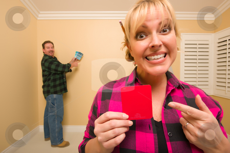 Couple Comparing Paint Colors in Empty Room stock photo, Fun Happy Couple Comparing Paint Colors in Empty Room - Woman Large, in Front, Man Smaller, Behind. by Andy Dean