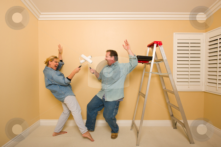 Fun Couple Playing Sword Fight with Paint Rollers stock photo, Fun Couple Playing Sword Fight with Paint Rollers in Room - Ladder and Paint Tray Near. by Andy Dean