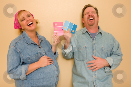 Pregnant Laughing Couple Deciding on Pink of Blue Wall Paint stock photo, Laughing Man and Pregnant Woman Deciding on Pink or Blue Wall Paint with Swatches in Hand.  by Andy Dean