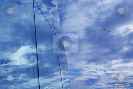 Reflection stock photo, Clouds and blue sky reflection in glass skyscraper by Kjersti Jorgensen