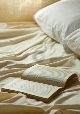 Bedtime story stock photo, Open book on a empty bed by borojoint