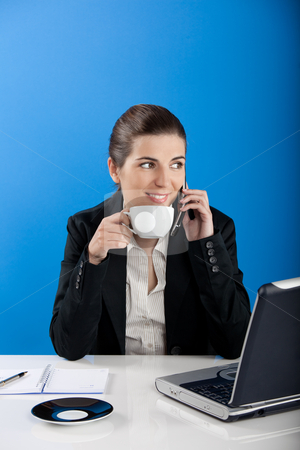 Businesswoman stock photo, Young business woman sitting in office drinking a coffee by ikostudio
