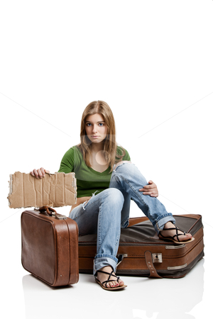 Hitch hiking woman stock photo, Beautiful young woman seated on the old suitcases holding a card tablet by ikostudio