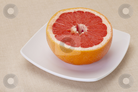 Cut red grapefruit stock photo, half of red grapefruit on white square bowl against tablecloth by Marek Uliasz