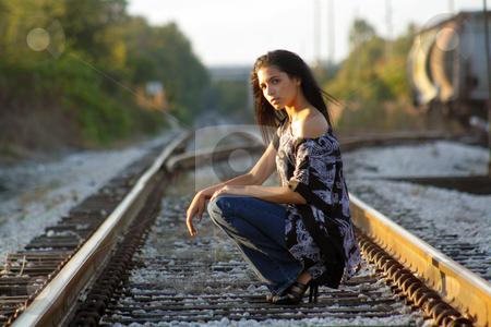 Beautiful Teen Latina on Railroad Tracks (1) stock photo, A lovely teenage Latina squats down on a railroad track, looking at the camera. by Carl Stewart