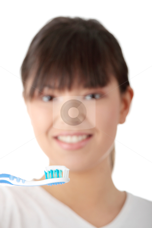 Washing her teeth stock photo, Young beautiful woman washing her teeth with blue brush, isolated on white background - focus on brush