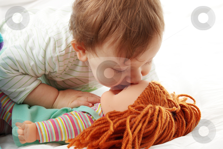 Baby girl stock photo, Baby girl kissing her doll isolated on white background by Piotr_Marcinski