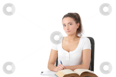 Young woman learning at the desk stock photo, Young woman learning at the desk with book and note pad, isolated on white  by Piotr_Marcinski