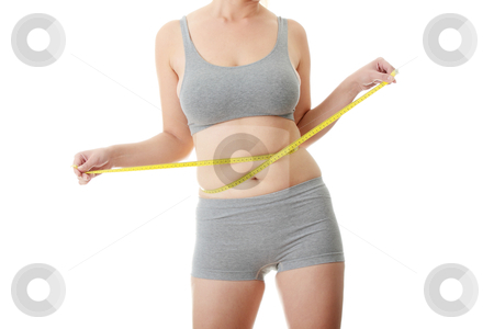 Woman measuring her waist stock photo, Woman measuring her waist isolated on white  by Piotr_Marcinski