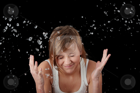Teen girl washing her face with water stock photo, Teen girl washing her face with water, isolated on black by Piotr_Marcinski