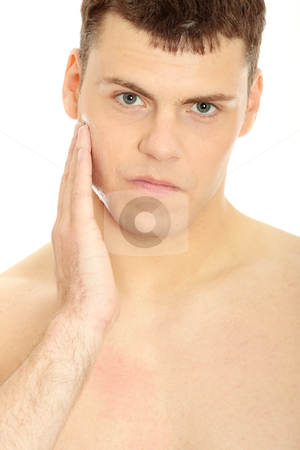 Skin care stock photo, Happy man after shaving applying moisturizing cream upon his face  by Piotr_Marcinski