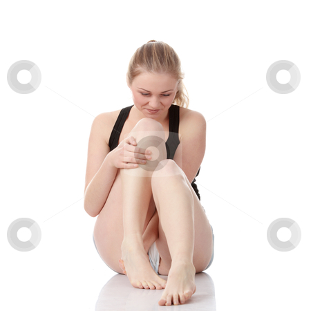 Woman experiencing leg cramp stock photo, Beautiful young blond woman experiencing leg cramp after a physical activity, isolated on white background