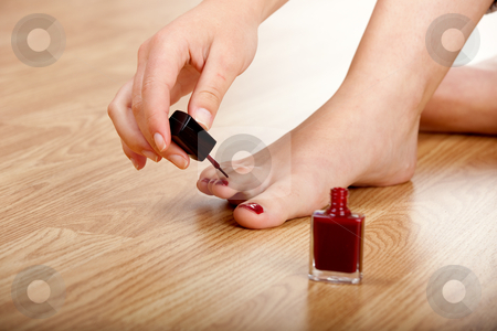 Applying red nail polish  stock photo, Woman applying red nail polish isolated on herself by ikostudio